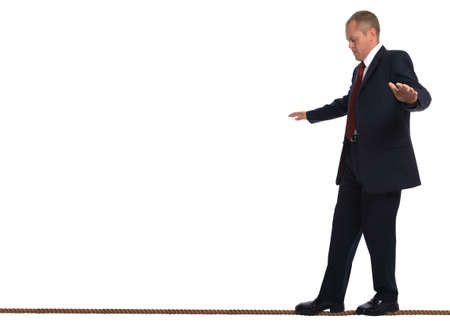 Businessman walking along a tightrope trying to keep his balance. Stock Photo