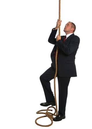 upward struggle: Businessman looking to climb to the top of a rope.
