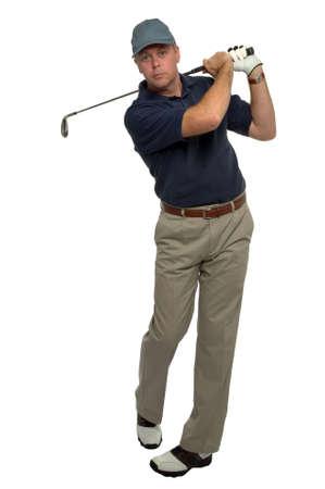 golfing: Golfer in a blue shirt, swing follow through after an iron shot.