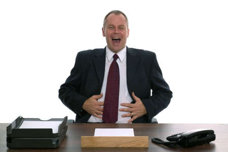 unsatisfied: Businessman sat behind a desk laughing. Concept of Helpdesk, Customer service, Complaints Dept etc