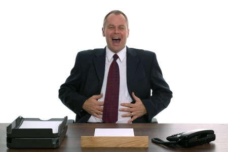 Uomo d'affari seduto dietro una scrivania ridendo. Concetto di Helpdesk, il servizio clienti, etc Dip Reclami