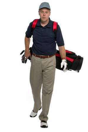 Male golfer walking along carrying his bag.