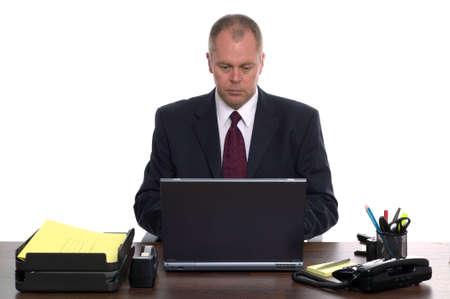 super highway: Businessman sat at his desk using a laptop computer.