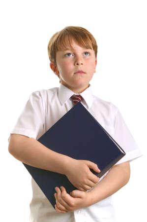 reference book: Un joven escolar de la celebraci�n de un libro de referencia, levantando los ojos