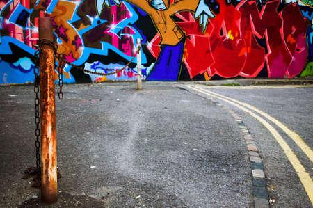 asbo: Inner city scene of urban graffiti spray painted on a wall.