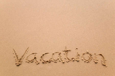 The word Vacation written in sand at the beach. photo