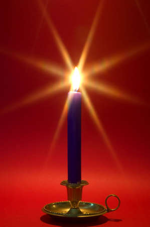 Blue candle in a brass holder alight against a red background. Christmas theme. photo