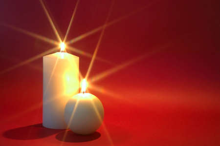 advent candles: Two white candles burning against a red background. Christmas theme.