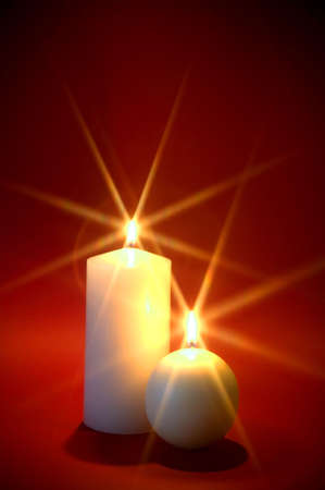 light columns: Two white candles burning against a red background, Christmas theme.