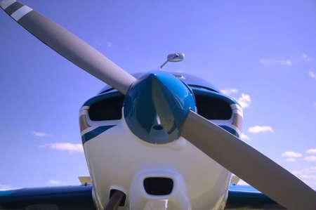 Close up of a light aircrafts nose cone against a blue cloudy sky. photo