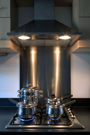 oven and range: Moderm kitchen brushed steel gas hob and overhead extractor fan, pots and pans cooking away.