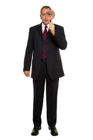 verify: Uomo d'affari utilizzando una lente di ingrandimento per uno stretto controllo.  Archivio Fotografico
