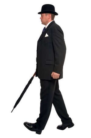 City businessman in pin striped suit wearing a bowler hat and carrying an umbrella as he walks along.