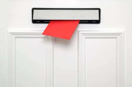 the through: Red letter coming through a chrome letterbox on a white door.  Stock Photo