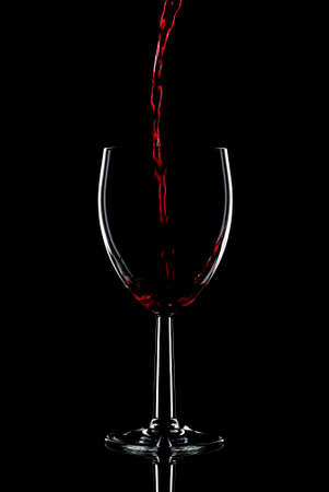 Low key shot of red wine being poured into a glass against a black background.