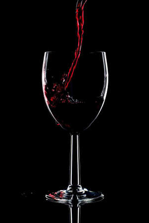 Red wine being poured into a glass and splashing over the side. Low key black background. photo