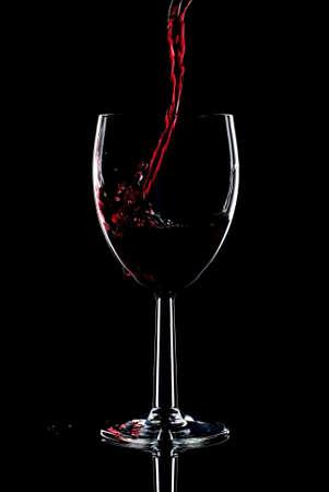 derrames: Vino tinto que se vierte en un vaso y salpicar por la borda. Baja clave fondo negro.  Foto de archivo