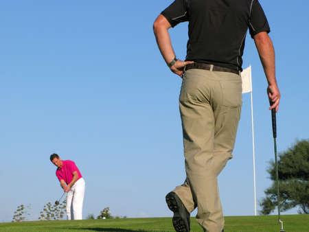 Golfista viendo su oponente tomar un largo putt difícil.