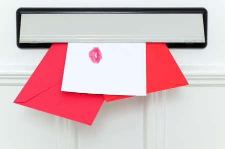 Valentines cards coming through the letterbox, one sealed with a kiss. Stock Photo