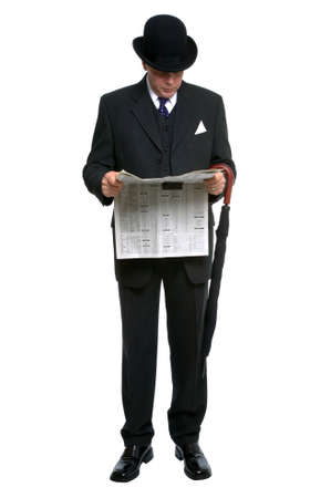 Businessman in bowler hat and three piece pinstripe suit reading a financial newspaper. Stock Photo