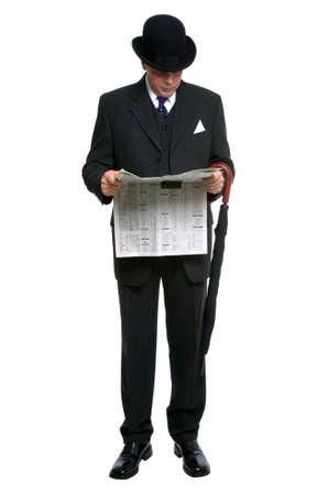 caballeros: Hombre de negocios en sombrero de jugador de bolos y juego de la tela a rayas de tres pedazos que leen un peri�dico financiero.