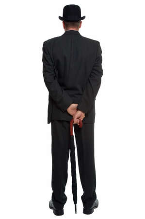 stereotype: Rear view of a man dressed in a pinstripe suit wearing a bowler hat and carrying an umbrella.