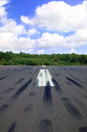 Empty runway with a line of trees and blue cloudy sky in the distance photo