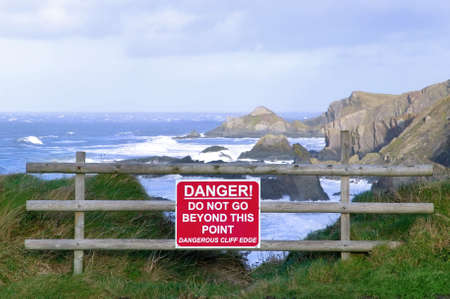environmental safety: Dangerous cliff edge with warning sign.