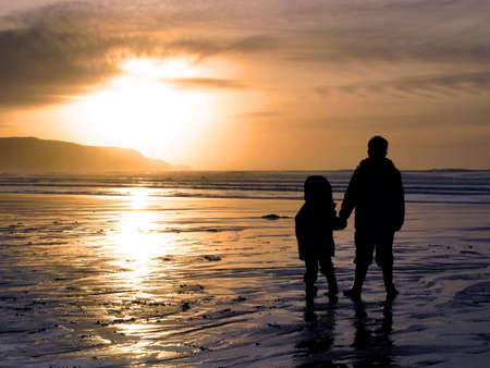 Two children holding hands whilst watching a beach sunset. photo