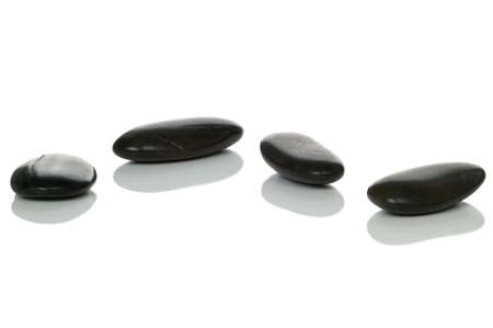 Four black pebbles with reflections on a white surface, high key shot.