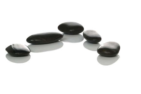 Five black pebbles with reflections on a white background, high key shot. photo