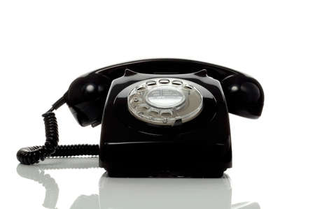 Retro black telephone on a white surface with reflection. photo