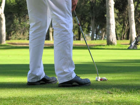 lining up: Close up of a golfer lining up a putt on the shaded part of the green. Stock Photo