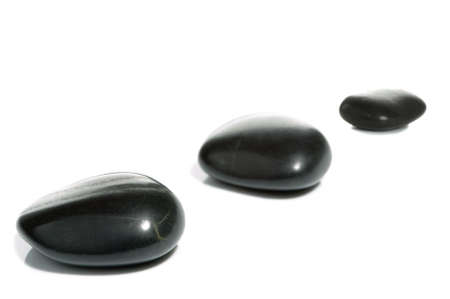 High key shot of three black pebbles on a white surface. Stock Photo