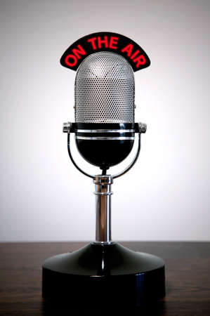 airwaves: Retro microphone with an On the Air illuminated sign on a desk, vignetted background.