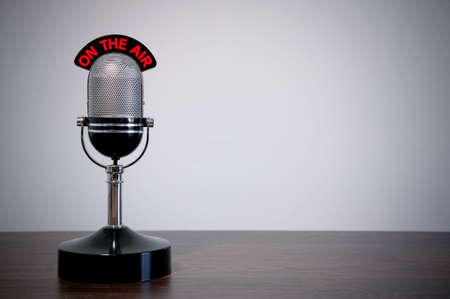 radio microphone: Retro microphone with an On the Air illuminated sign on a desk, vignetted background.