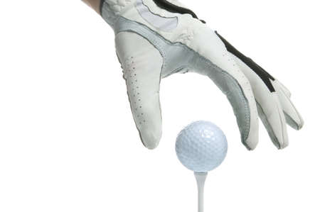 tee: Close up of a gloved hand putting a golf ball on a tee, high key shot.