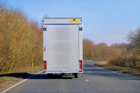 Delivery van with a roller shutter back driving on a road during a sunny autumn day.