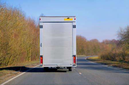 Levering van met een roller sluiter terug rijden op een weg tijdens een zonnige herfstdag. Stockfoto