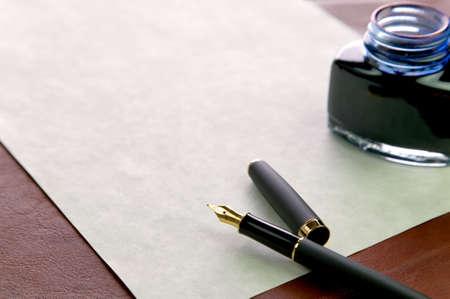 lettres en or: Or nibbed plume, papier filigrane cher et un encrier sur un cuir de bureau, shallow DOF, se concentrer sur les plumes.