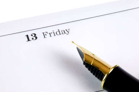 focal point: Friday 13th on a diary page with a gold nibbed fountain pen. Focal point is the date. Stock Photo
