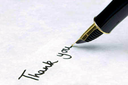 Thank You written on watermarked textured paper using a gold nibbed fountain pen. Focal point is on the text.