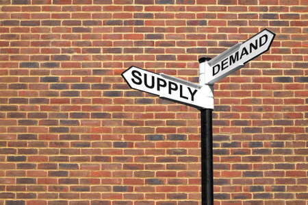 surplus: Concept image of a signpost with Supply and Demand against a brick wall