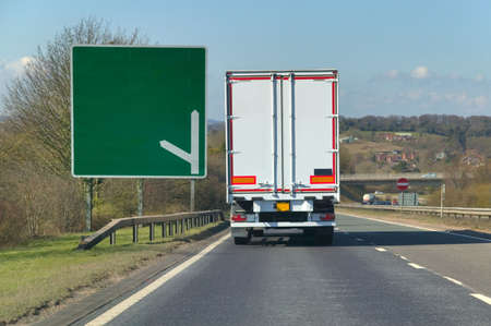 dual: White heavy goods lorry passing a signpost on a dual carriageway, blank for you to add your own text. Stock Photo