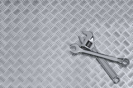 Mechanical background image of two spanners on a checkerplate workbench. Stock Photo