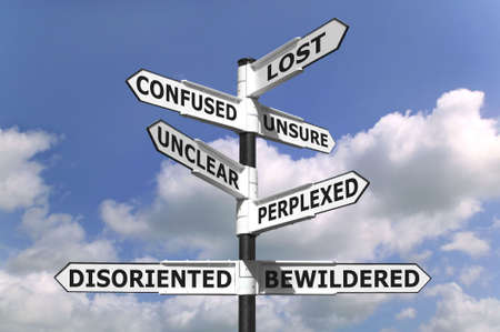 unclear: Concept image of a lost and confused signpost against a blue cloudy sky. Stock Photo
