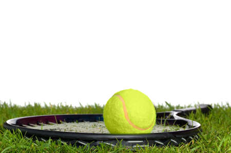 Surface level shot of a tennis racket and ball on real grass.