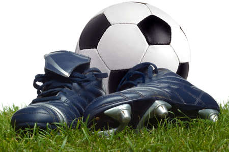 A pair of boots and a football on the grass, studio shot.