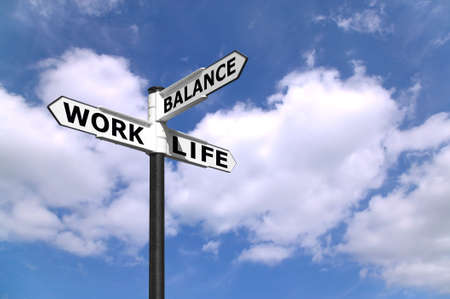 balance life: Concept lifestyle image of a signpost directing Work Life Balance against a blue cloudy sky.