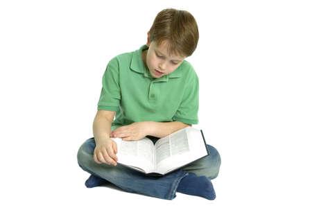 reference book: Boy de edad escolar primaria se sent� cruzado las piernas leyendo un libro de referencia, aisladas sobre un fondo blanco.